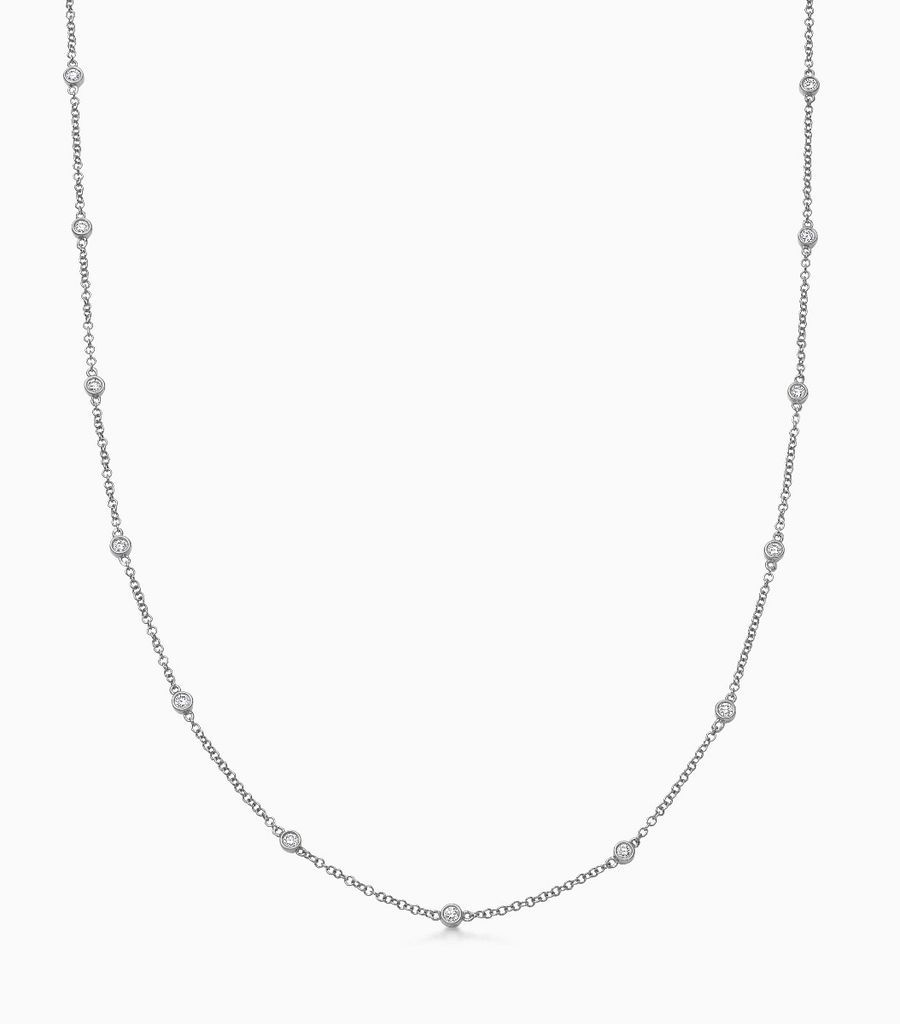 Diamond necklace, with 9 bezel set, faceted diamonds, dispersed along a 32inch, fine gauge, 18carat black gold chain. Total weight of diamonds 0.54 carats